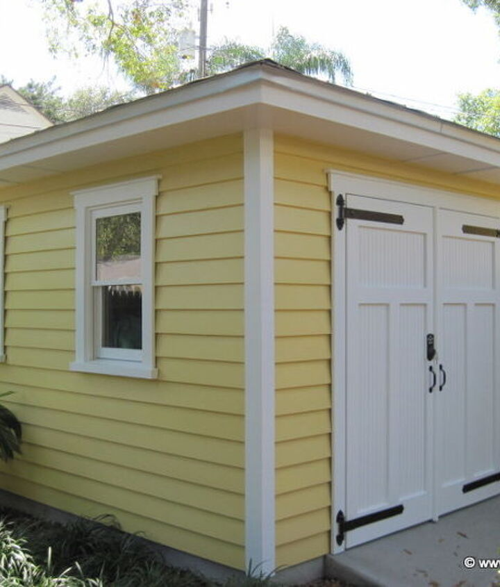 The shed has two wood windows on the side facing the yard