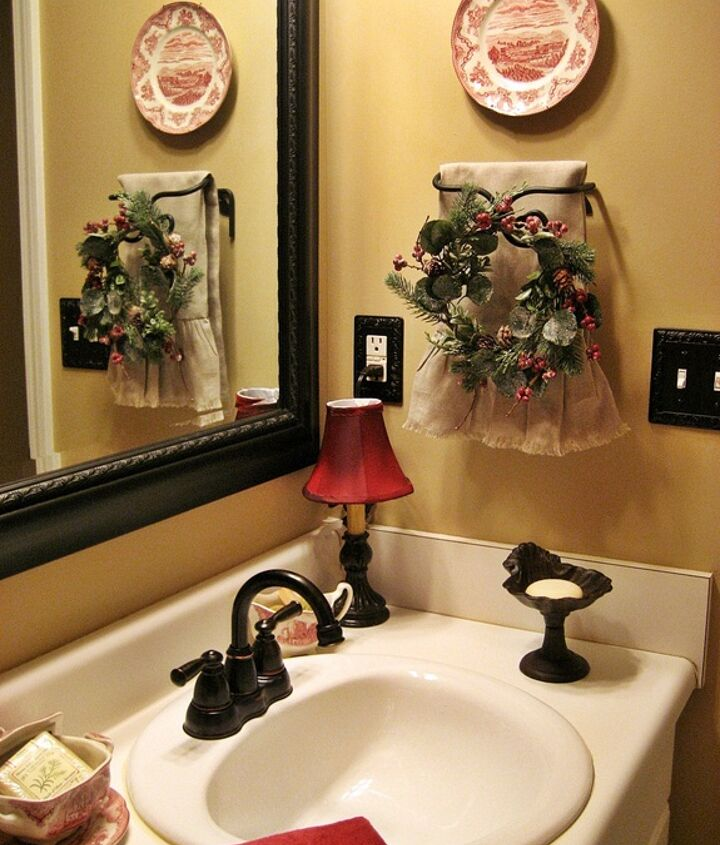 A mirror and fixtures in oil rubbed bronze continue the French country look. I added a small wreath to the towel rack for a little bit of Christmas along with another plate.