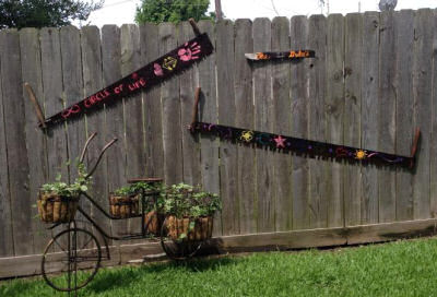 Neat old bicycle planter with hand painted saws on a wooden fence. Shared by Beth.