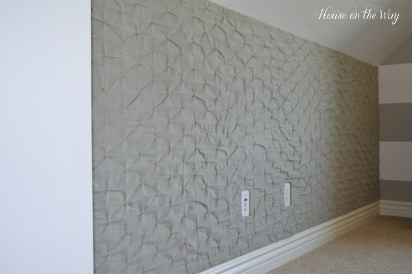 The entire wall is covered with foam board that has been covered with fabric, creating a giant pin board.