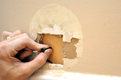 Slip a backer-board into the hole and hold it with a temporary screw.