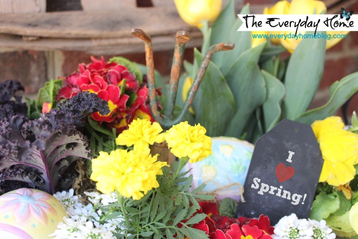A vintage red wire basket holds an assortment of Spring flowers and plants as well as a small chalkboard label and a vintage garden tool.