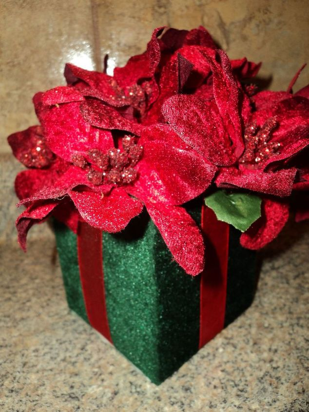 A Dollar store velvet gift box and velvet poinsettia sprigs. Just simply glue the florist foam on the bottom of the inside of the box.Cut to fit the sprigs in the foam, then glue them in making the arrangement. Done!