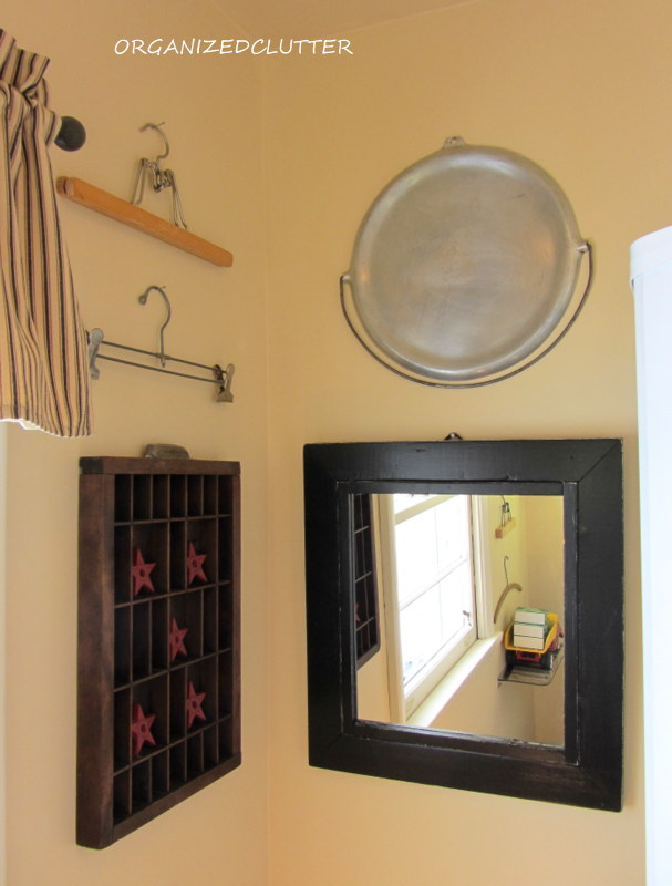 A few more hangers, a printer's tray, camp or wood stove griddle and a rustic black mirror.