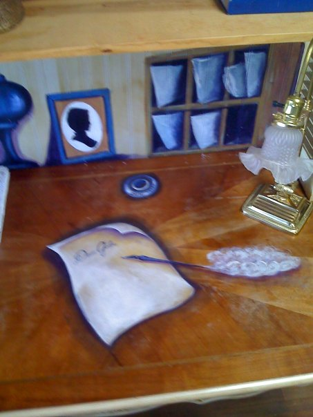 I painted a quill pen with inkwell and a dear John letter on the desktop, along with books, a plant, and a letter box to add interest filling the shelf.