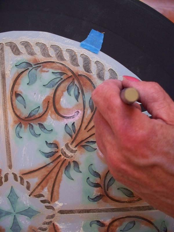 Using a medallion stencil, I added a round design to the top in pastel brown, green and gold metallic.