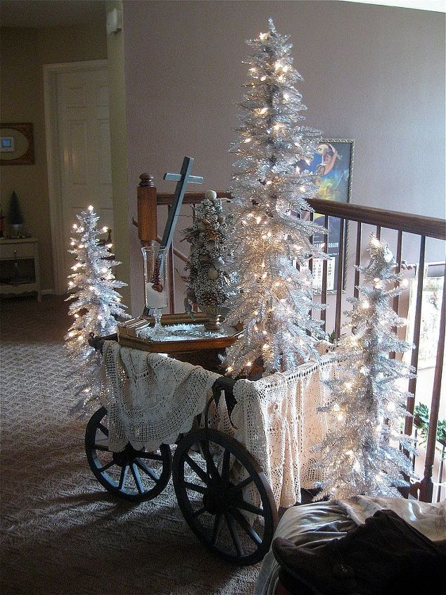 I created a winter vignette with my German goat wagon using silver trees from Hobby Lobby, lace, gold & silver accents and fake snow!