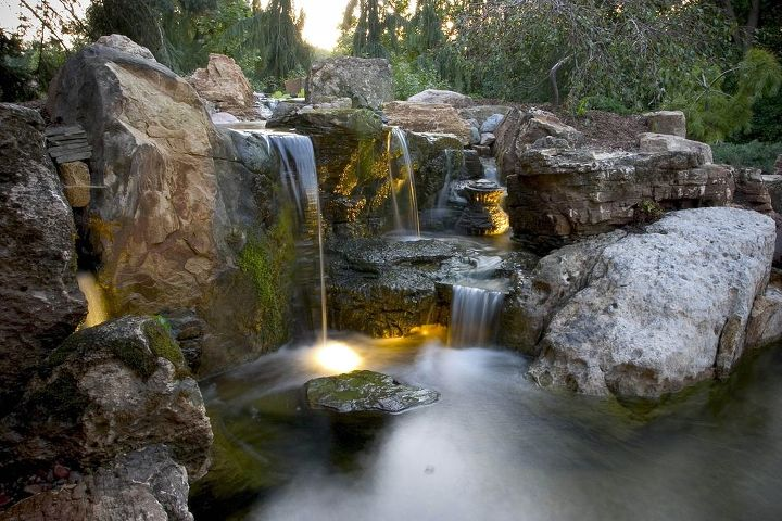 The rugged waterfalls fit in with the large evergreens on the property.