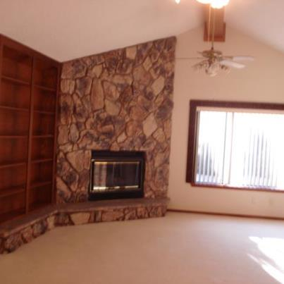 Left side of Living Room shows book shelf, fireplace,  rock wall, off center window,  vaulted ceiling.