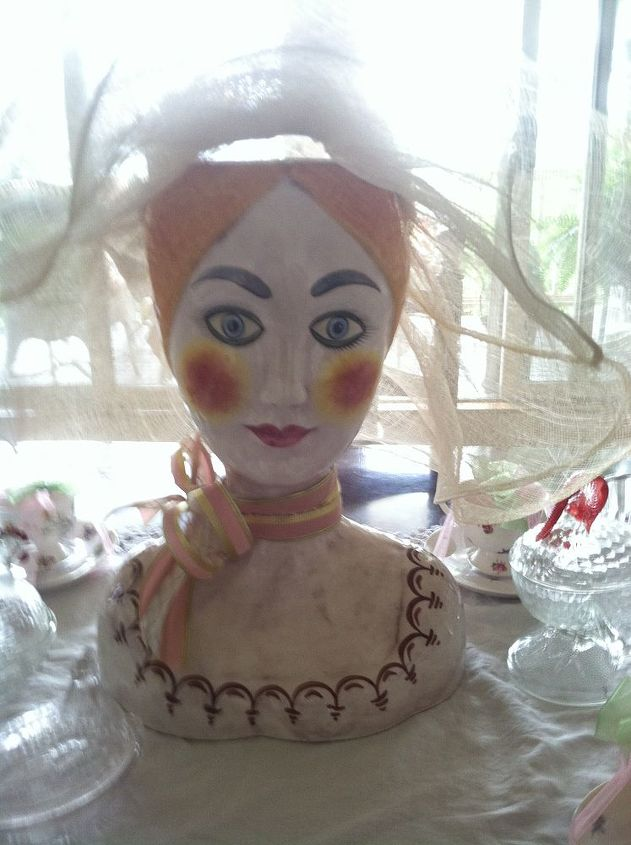 A delightful antique vase of a woman's face acts as the centerpiece in the dining room. So pretty.