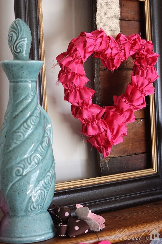 I hung my Ruffled Satin Hearts over the photo frames with a pushpin. I loved making them a few years back. The little leather flower is from our wedding. And the aqua decanter is from a yard sale.