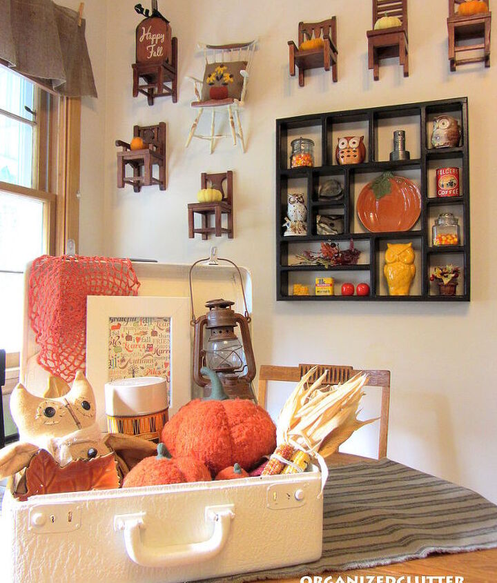 On the wall with the shadow box, Pottery Barn chairs with mini pumpkins, a Black Eyed Susan pillow and fall sign.  On the table, a fall suitcase vignette.