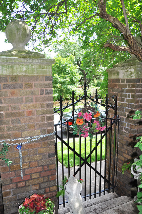 Brighton up and existing gate with a colorful wreath or a sculpture looking out onto the street.