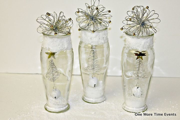 adding christmas decorations to the inside of the vases by tying the spiral trees to the