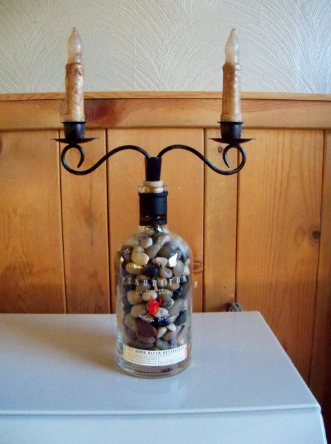 """filled with polished rocks, black distressed metal candleholder, 4"""" grunge candles that are battery operated."""