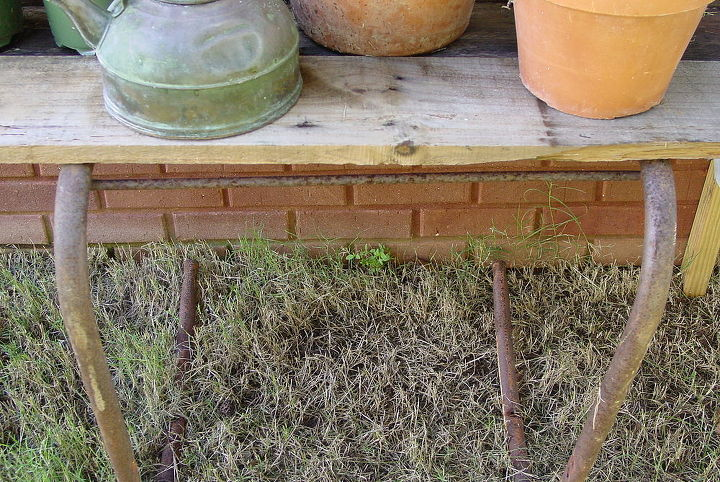"""My shelves to the left of the """"Pot House"""" are made from leftover boards. The table underneath is supported by the legs from the old green metal chair and the top is pallet wood."""