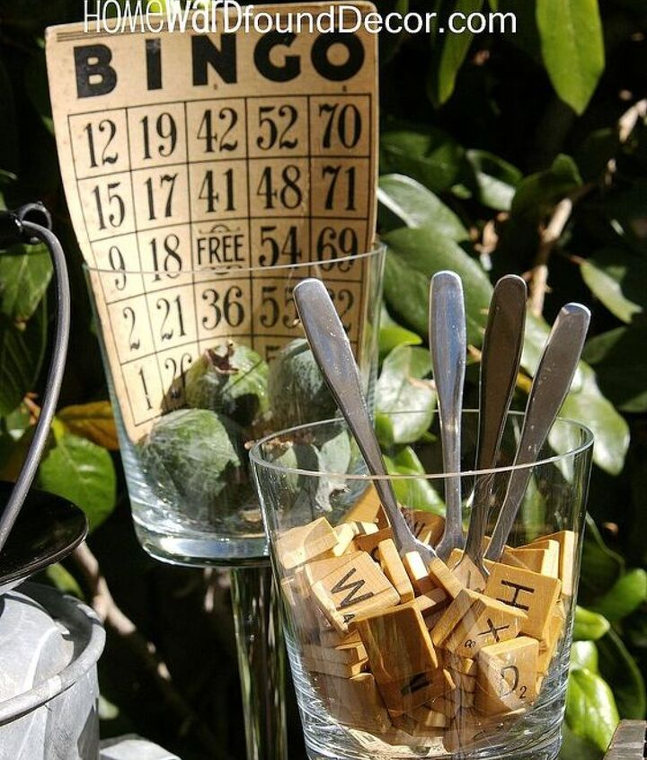 Scrabble letter tiles in a clear footed votive holder hold cheese knives at an appetizer buffet.