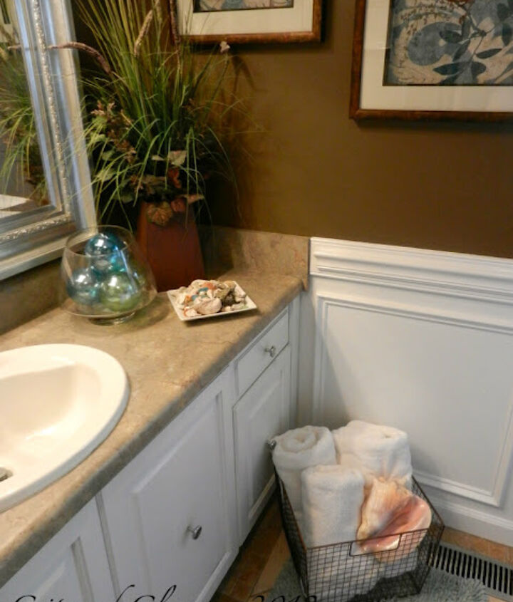 A brown and blue bathroom is the perfect setting for fluffy white towels.