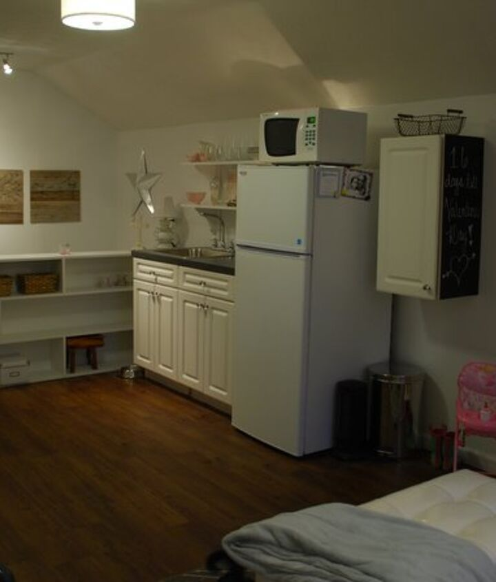 "The other side of the room has a small ""kitchen"" area.  The cabinets were purchased from the Habitat for Humanity ReStore and the refrigerator was free.  The book case separates the stairway from the room."