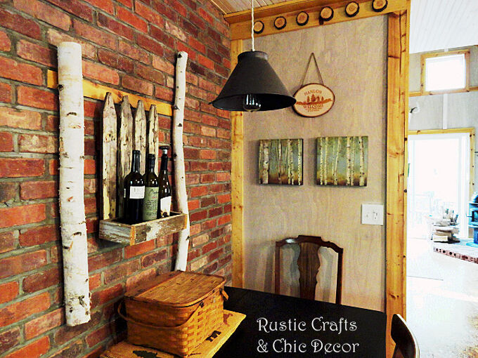 how we blended his rustic and her chic in our cabin decor, home decor, repurposing upcycling, I tried to re create the look of a favorite cafe with a brick wall and then I added some chic wall art with birch logs an old planter box and wine bottles The light fixture was made from an antique kitchen sifter