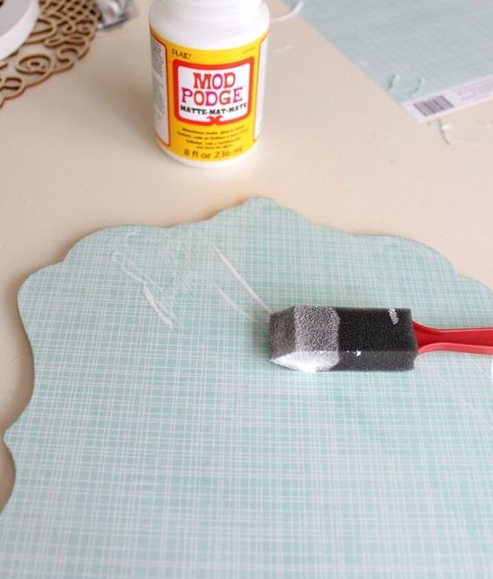 Attach scrapbook paper to plaque with mod podge.