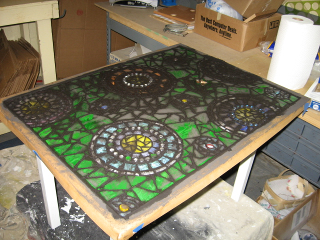 stained glass mosaic patio table, painted furniture, tiling, The round glass gems did not want to adhere well with only Weldbond glue Several popped out during grouting I used Mighty Putty to reset them and it worked really well since you can use it wet or dry
