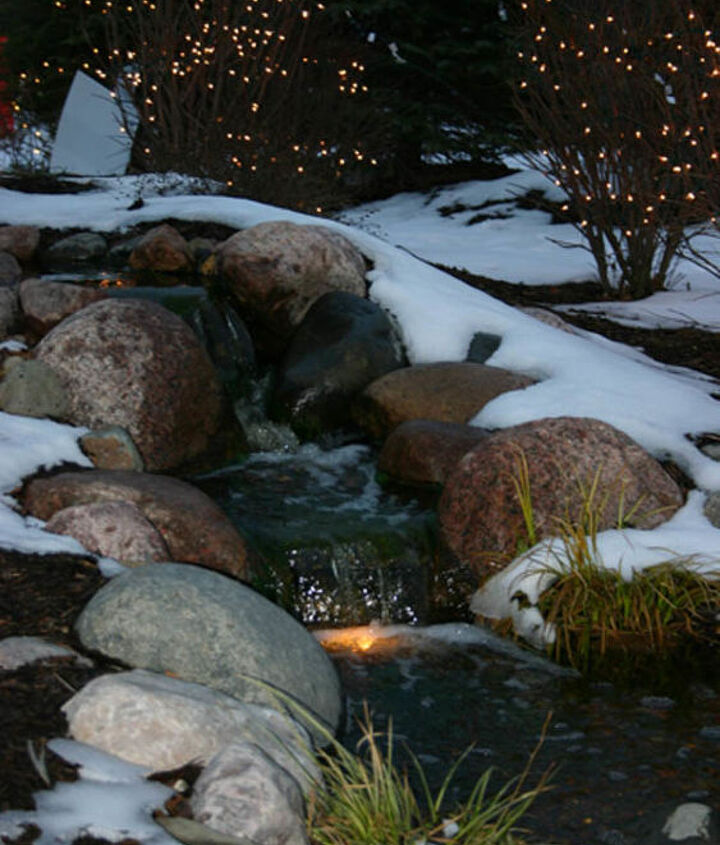 A small waterfall looks inviting during the winter with the use of underwater lights.