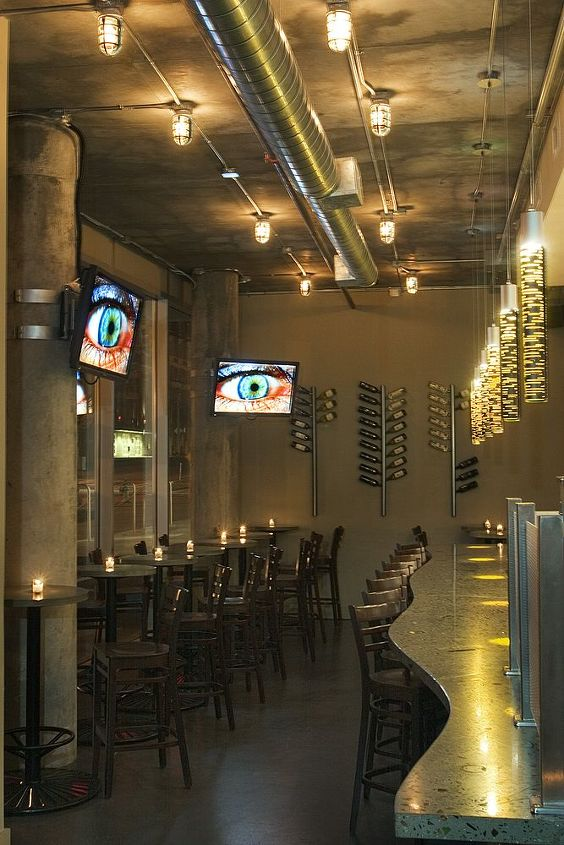 Bar in Mid City Cafe, fabricated in gray concrete with wine bottles and glasses mixed in. There are bottles in profile and glasses sliced in half so you see the full profile in the concrete.