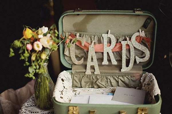 Still speaking of shabby chick and rustic decorations, using an old suitcase to hold the greeting cards from the guest is both original and budget-friendly.