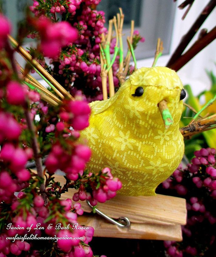 tiny fabric bird with beak, wings and tail made out of twigs