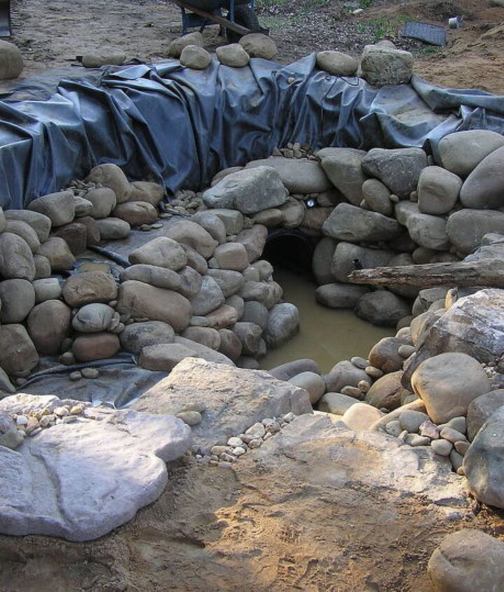 Underlayment, liner and then rock is our process to a sound Pond foundation. Notice the fish cave in the corner of the pond, a place of refuge for our finned friends.