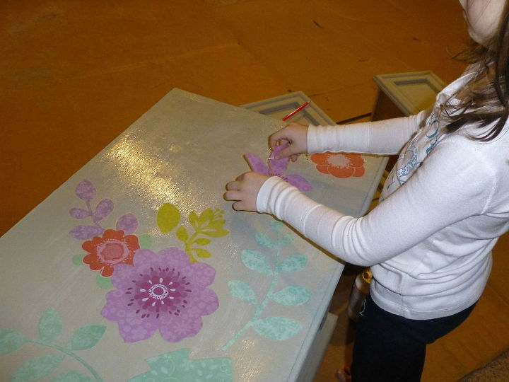 To cover the damage on the top, she put flowers on with Mod Podge.  (The hardest part is letting her do it herself!)