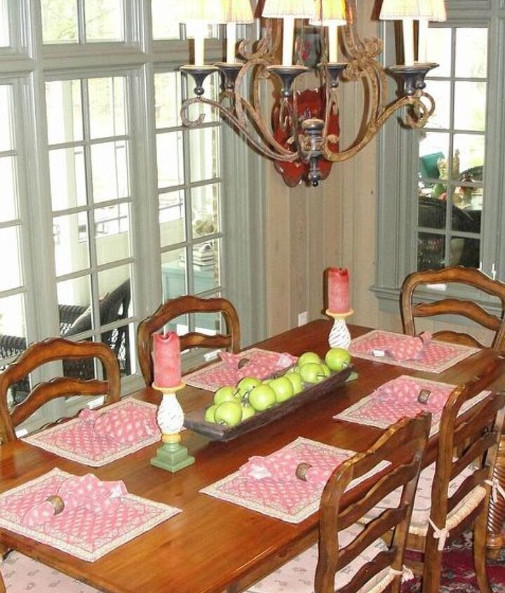 An antique dough bowl holds faux green apples.  The windows open onto the back screened porch.
