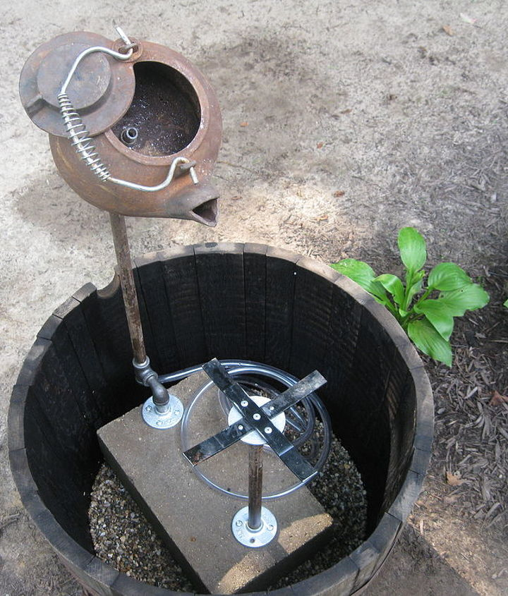 We then built a support for the gold pan and dropped the unit into the whiskey barrel. We added a fountain pump and inserted tubing up through the tee on the bottom of the pipe that supports the tea pot and into the tea pot.