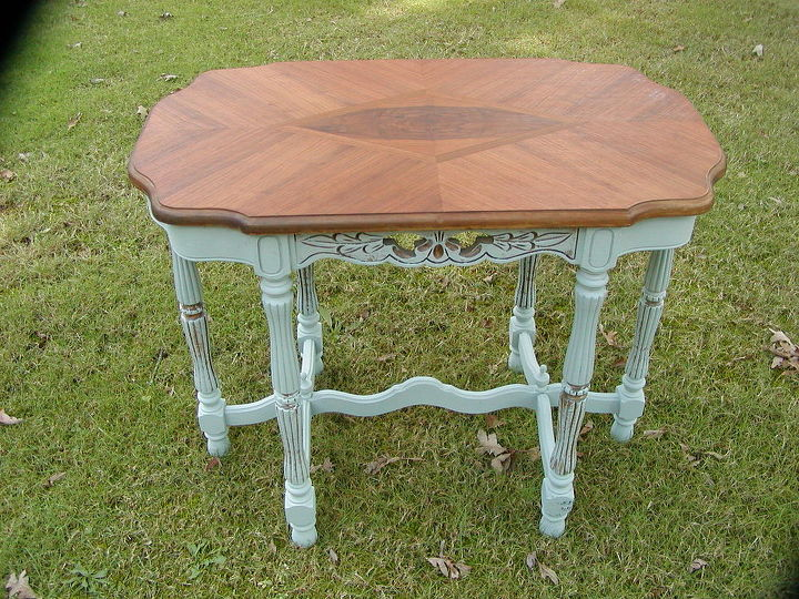 The turn of the century parlor table is finished and stained on its veneer top that contrasts beautifully with its chalk painted base.