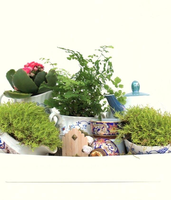 A tea pot mini garden using a tea pot, tea cups, creamers and sugar bowls.