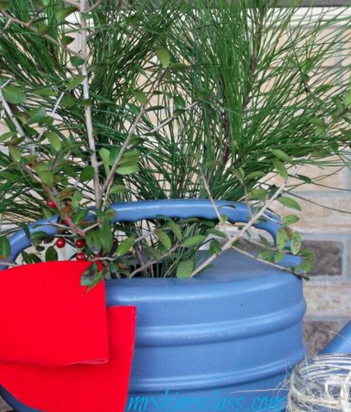 fresh cut pine boughs and holly branches make this blue, plastic watering can look like charming cottage Christmas decor.