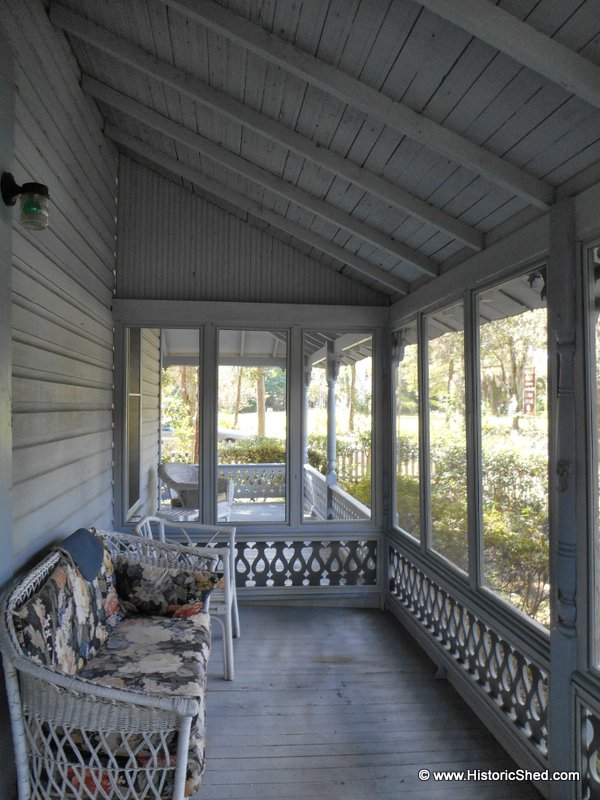 A new railing that matches the existing separates the screened porch from the open porch.