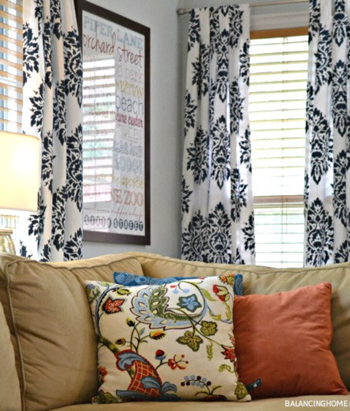 Plain white drapes get dressed up with a stencil and craft paint and bring some color, drama & much needed personality to my living room.
