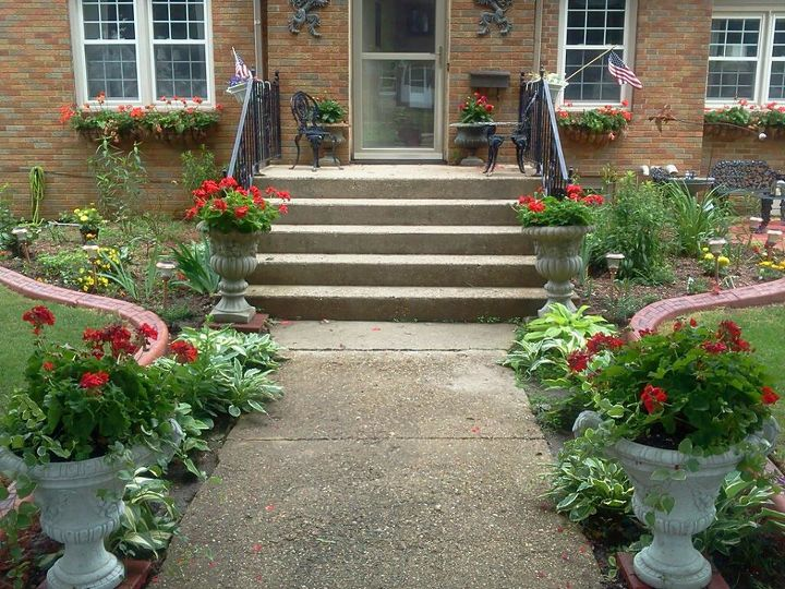 I had different vareties of hosta plants along the front walk, installed two large urns at the end of the walkway with red geraniums, vinca vine, and purple wave petunias.
