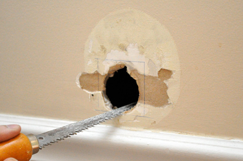 Squaring the hole makes it easier to fit a new piece of drywall.