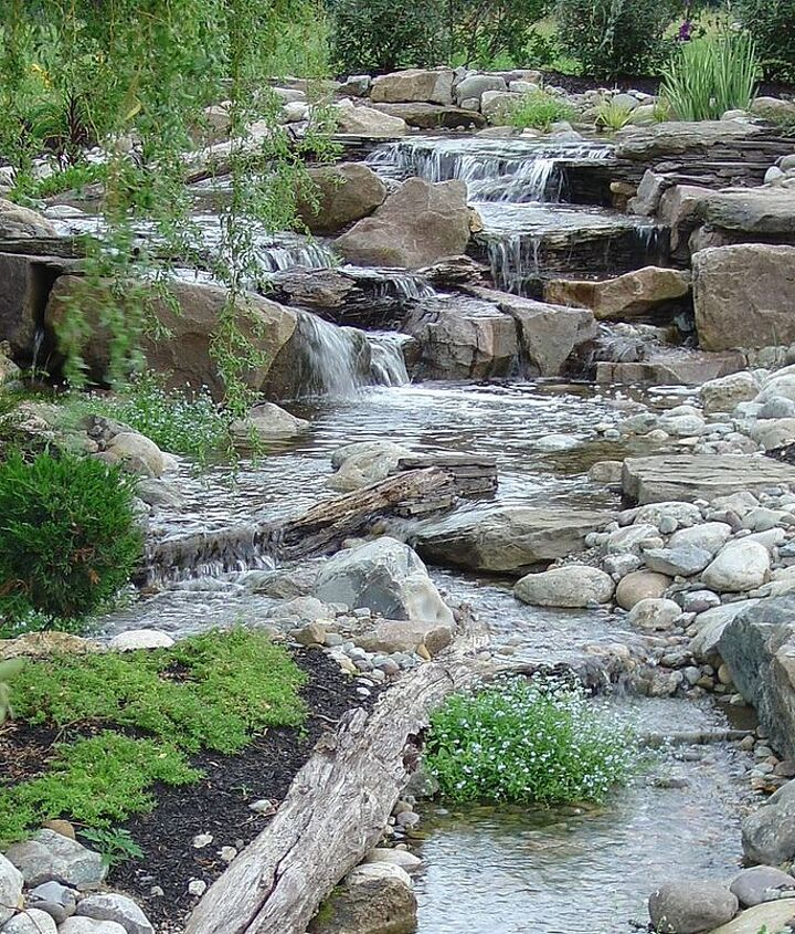 Logs and stumps help to naturalize this waterfall and stream.  Learn more about our waterfall construction, click on this link https://www.facebook.com/notes/bjl-aquascapes/waterfalls-waterfall-contruction-pondless-waterfalls-high-end-
