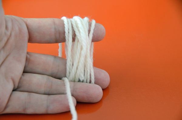 Begin by winding the wool around two fingers.