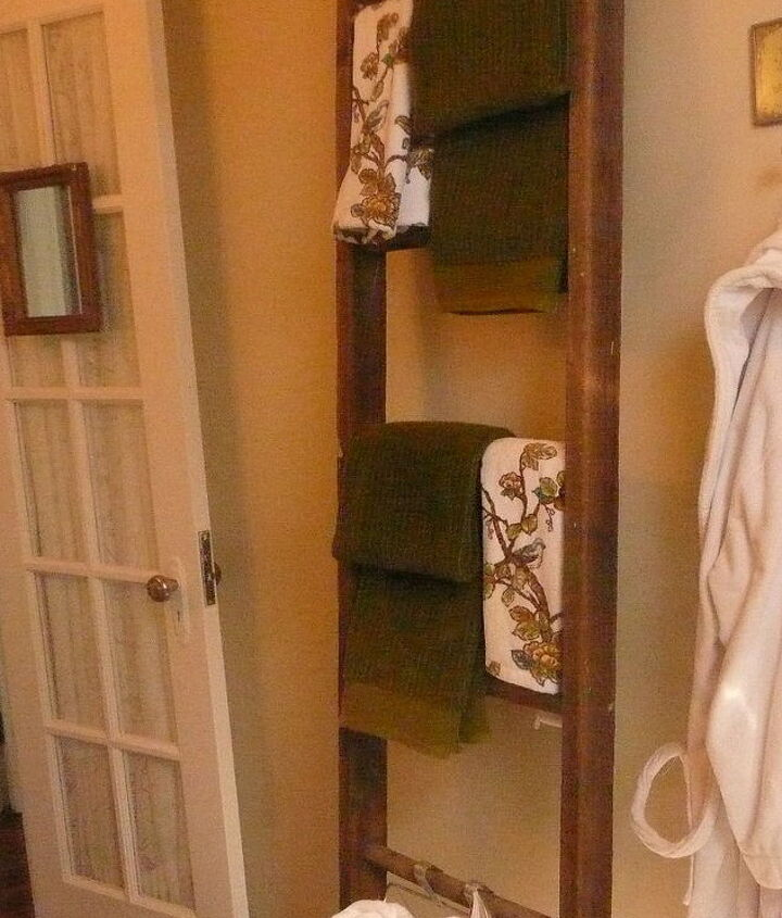 A glass paned door with a stretch panel replaces the original, and a vintage ladder functions as a towel bar.