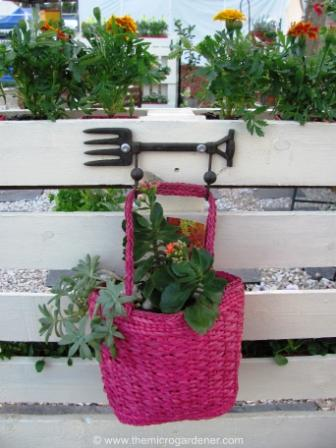 I added decorative garden hooks to hang this upcycled handbag planter with succulents and other garden art.