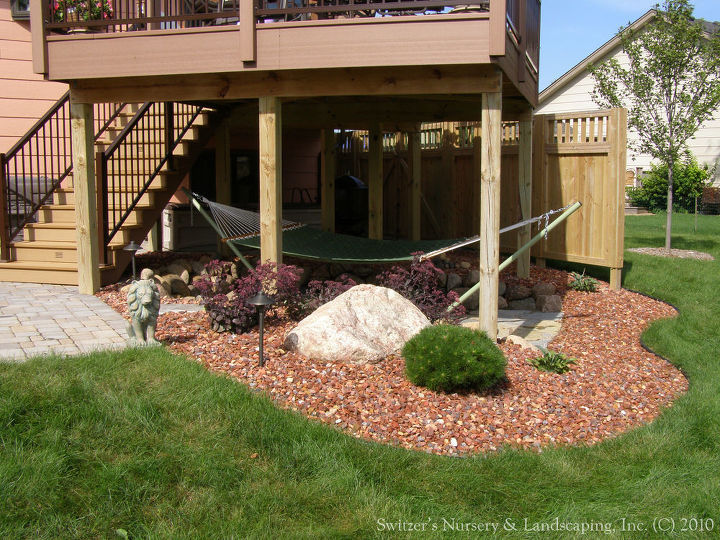 Incorporating the space under the deck can make the maintenance that much easier.  The space can be delightful and pleasing to look at as part of the landscape.