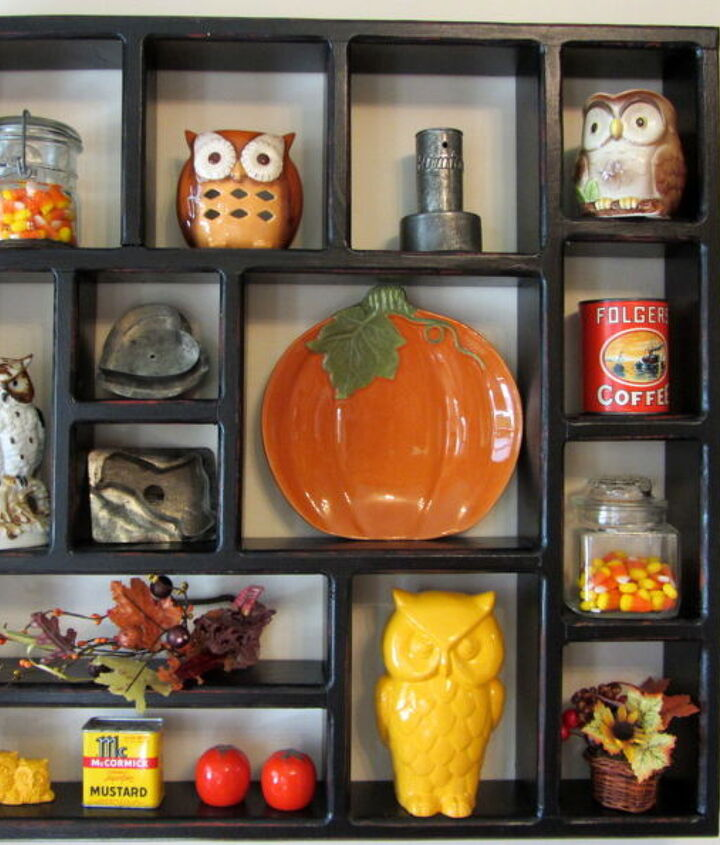 A shadow box with candy corn in jars, vintage tins, Folger's Coffee puzzle in an orange can, fall faux foliage, an orange pumpkin plate and my owls.
