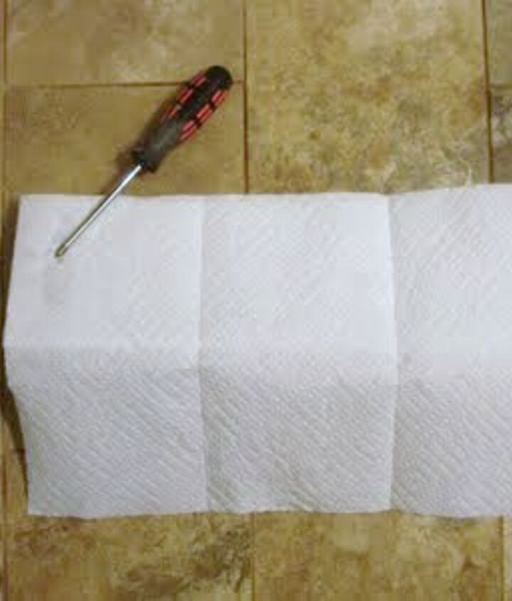 I tore off a few sheets of paper towels the same length as my hook (select-a-size paper towels work best).  *Be sure to place the paper towels level with the top of your wall hook.  Then using my screwdriver, I marked a spot on the paper towel for each hook.