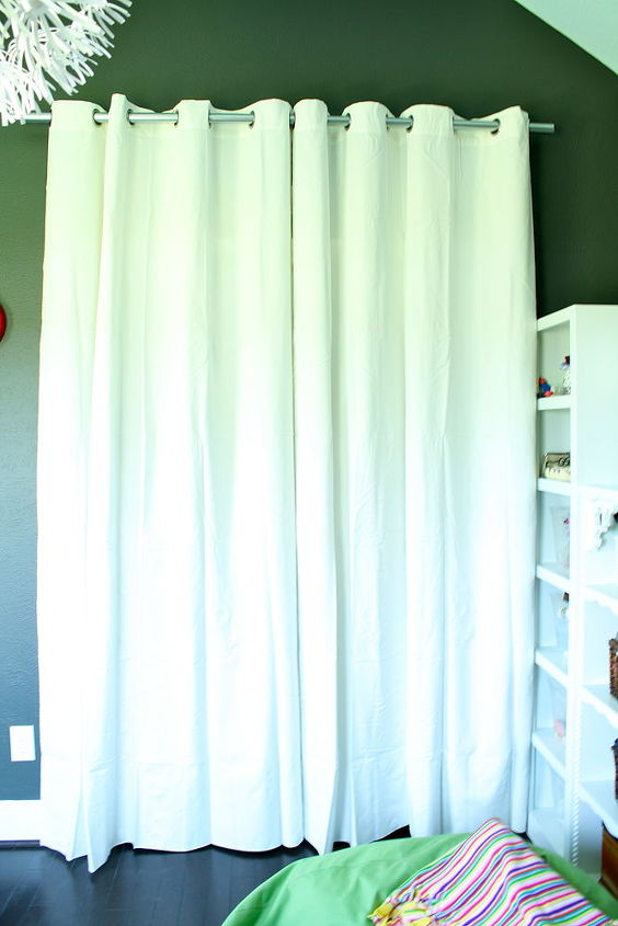 We used an IKEA curtain with a fence post rod to hide her closet.  The original doors took up too much room.