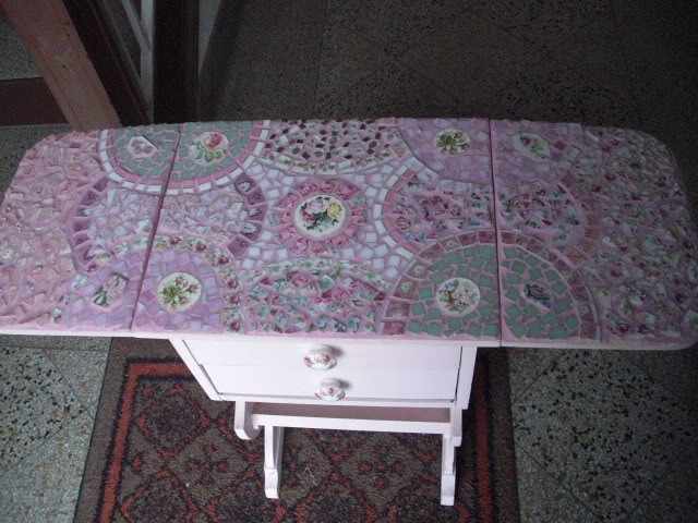 This is a vintage sewing table.  I painted it, mosaiced it and then added handpainted rose doorknobs.